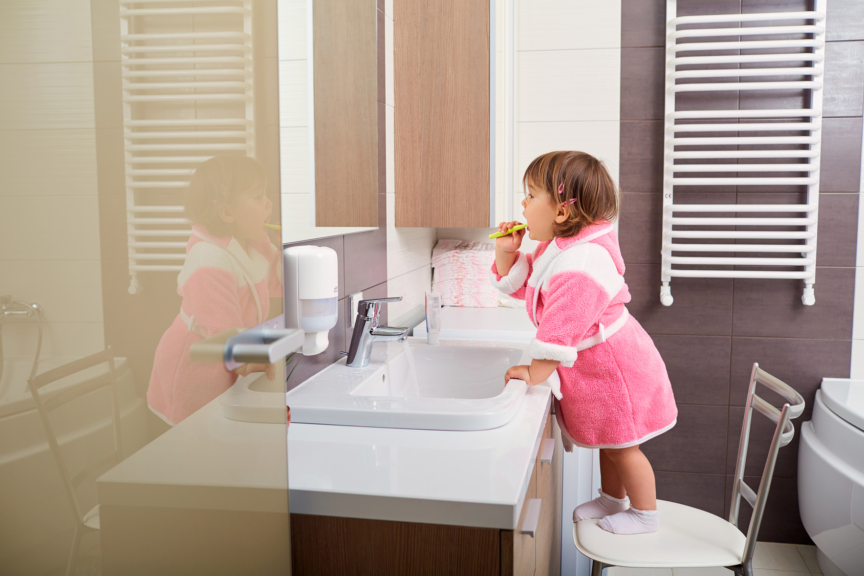 Child cleaning teeth in bathroom.