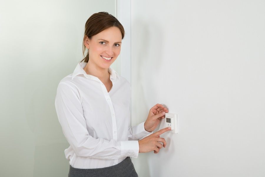 Businesswoman Setting The Temperature On Digital Thermostat