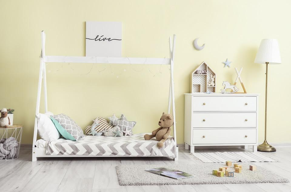Interior of modern children's room with comfortable bed and chest of drawers